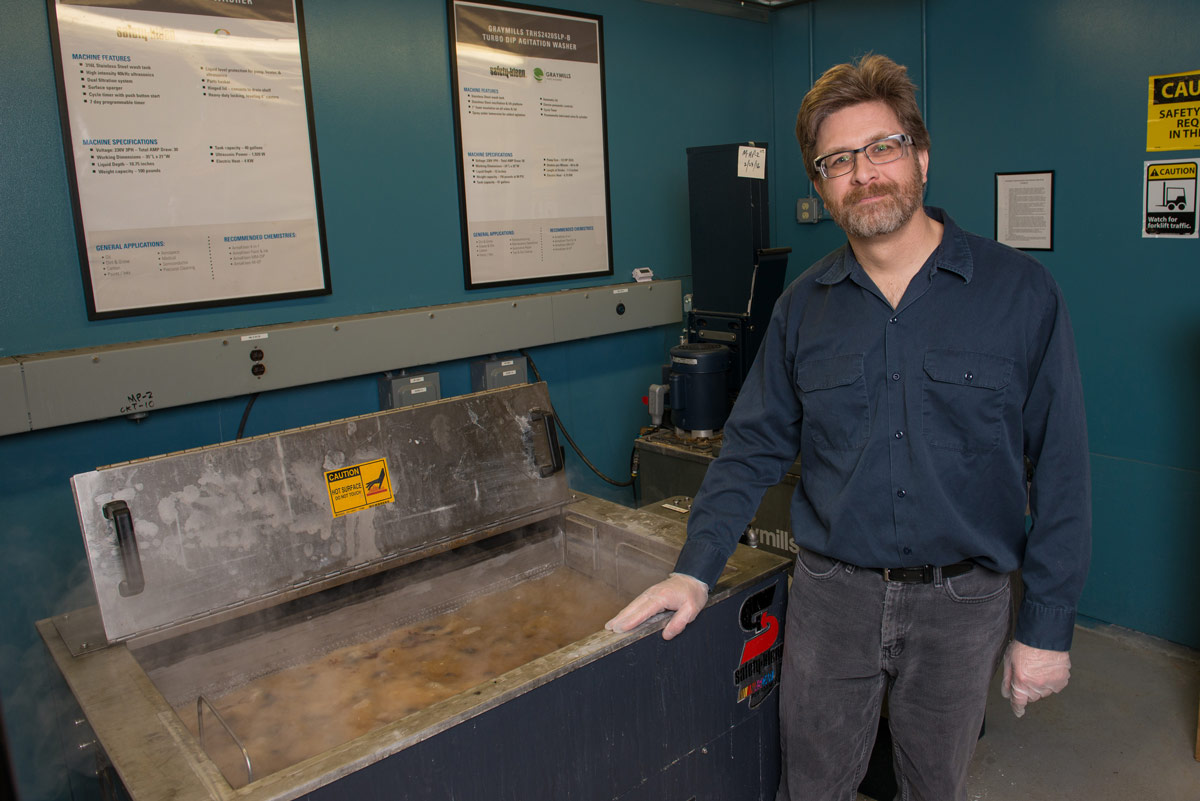 Andy Logan inspects the cleaning solution in an aqueous cleaner.